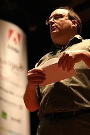 Jared Spool on stage opening an envelope.